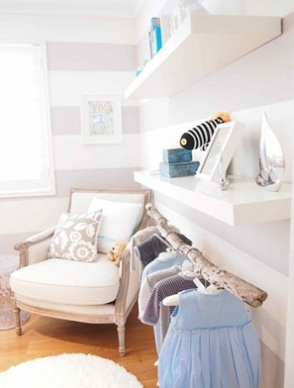 small nursery idea - hanging clothes under a bookshelf with a wood branch - so cute