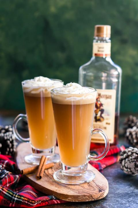 Slow Cooker Hot Buttered Rum in Irish coffee glasses with a bottle of spiced rum in the background