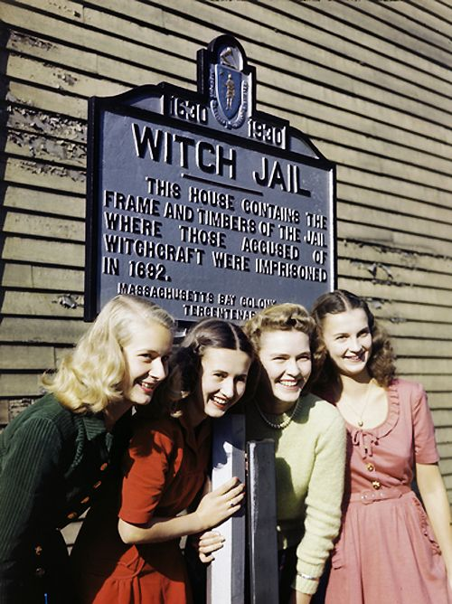 Girls pose by a jail that recalls the witch trials of 1692 in Salem, Massachusetts. Photo taken in 1945.