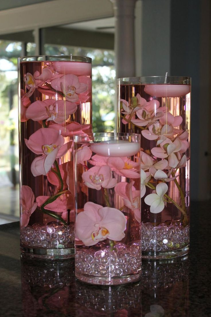 Pink-tinted water with jewels and orchids with a floating candle!  The different sizes help to add a bit of flare!