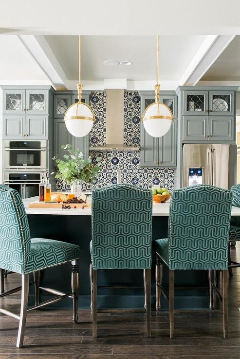 Blue and gray kitchen features gray raised panel cabinets adorned with brushed brass hardware paired with white quartz countertops and a blue Mediterranean style mosaic tile backsplash, Fireclay Grandola Tile.