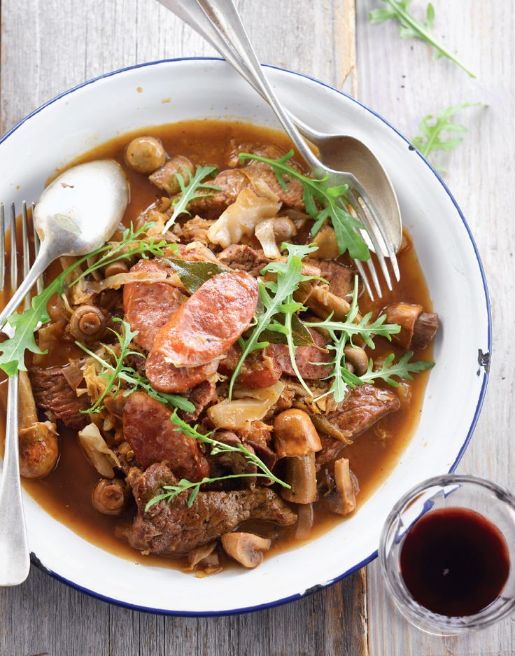 Bereiden: Maak de champignons schoon met keukenpapier en halveer ze. Breng de zuurkool aan de kook met ½ liter water en laat 15 minuten koken. Verhit ondertussen 2 el olie in een grote pan en fruit de witte kool, de ui, de champignons en de pruimen 10 minuten. Verhit de rest van de olie in een pan. Voeg fijngesnipperde knoflook toe. Bestrooi het vlees met peper en zout en bak rondom bruin. Schep het vlees om met de knoflook en haal uit de pan. Blus de pan met 50 ml rode wijn en roer he...