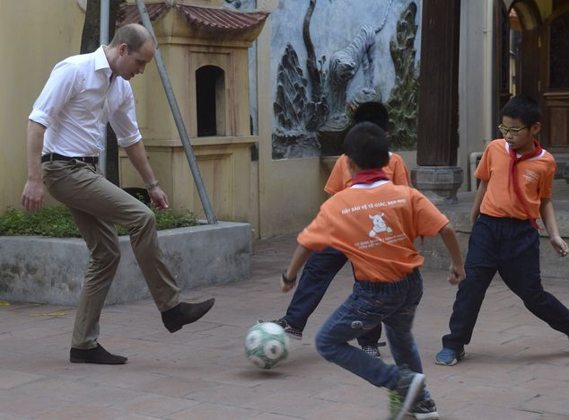 Britain's Prince William, Duke of Cambridge, plays soccer with pupils during his visit to ...