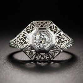 Something distinctively different in an original Art Deco diamond ring, circa 1920s-30s. Die-struck and hand-tooled in 18K white gold, the chamfered octagonal mounting is thoroughly adorned with both curved and geometric filigree, culminating on top with a bright white and sparkling European-cut diamond weighing a quarter-carat. Currently ring size 5 1/4, this one can only be sized one size up or down.