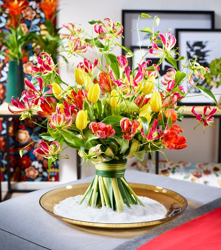 Happiness: Kalendarisch zieht sich der Winter bis zum  20./21. März – auch wenn wir schon mit Jahresbeginn den Frühling kaum mehr erwarten können. Die Freude an der erwachenden Natur bringt dieser farbintensive Blütentanz aus Gloriosa und Tulpen zum Ausdruck.   Seine leichte Optik erhält der Strauß durch seine lockere, verspielte Form. Die mit einem Phormium-Blatt ummantelte Bindestelle gibt diesem Format besonderen Reiz.   Ein Strauß voller Optimismus, Freude und positiver Gefühle…
