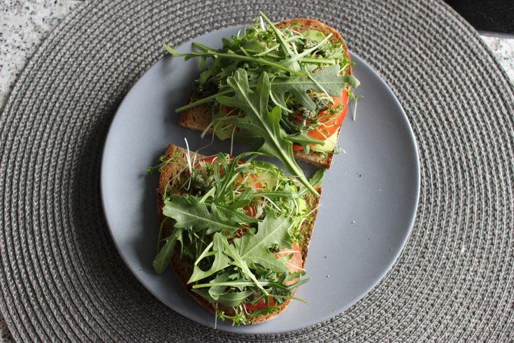 Берем черный хлеб, смазываем его песто или каким травянным соусом, режем тонко томаты и авокадо, добавляем рукколу и kresse