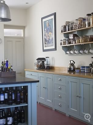 Kitchen cabinets hand-painted in Farrow & Ball's 'Green Blue' No.84, topped by a combination of honed African black granite and wide plank European oak worktops.
