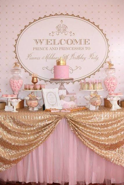 gold/pink table, white serveware, sign in the back, candy table