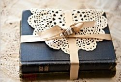"""Old hardcover Bible covered in a vintage doily and pretty satin ribbon as a """"ring pillow"""". Pretty cool."""