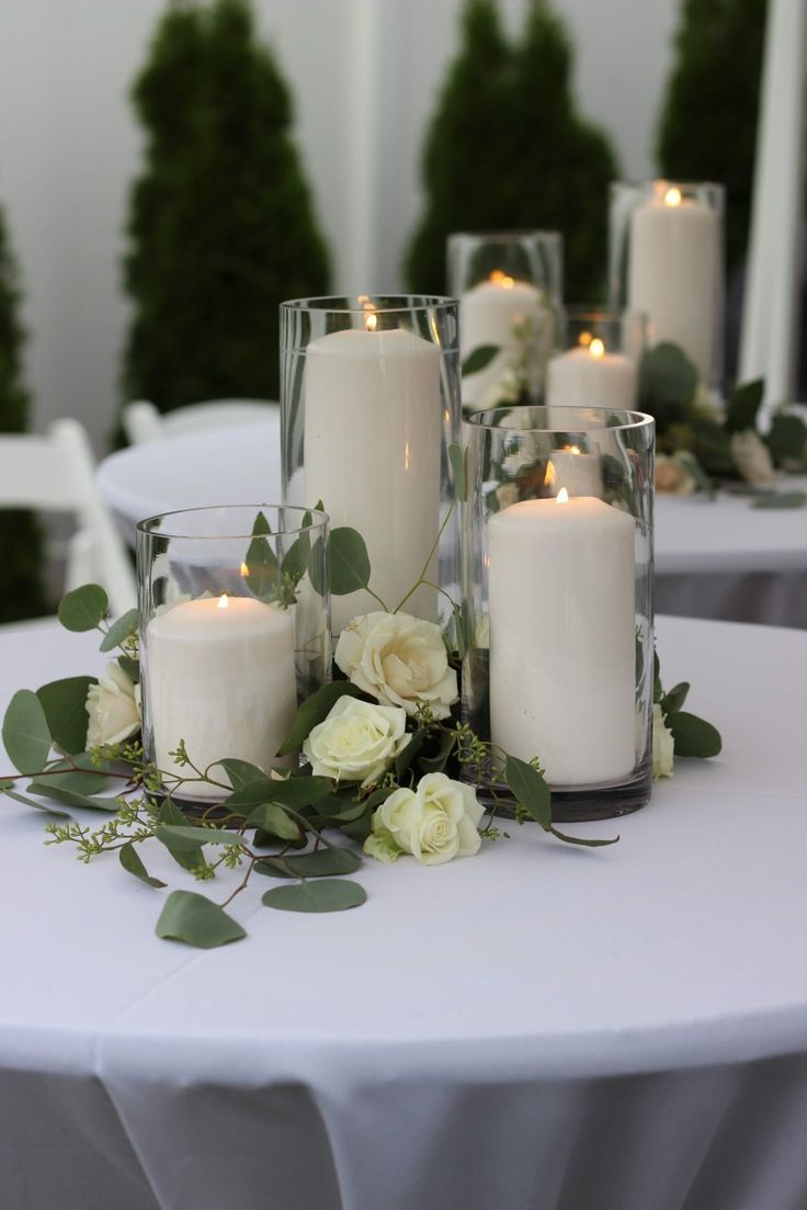 Glass Cylinders Filled With Candles And Surrounded By Greenery And Roses White Wedding Decorations Romantic Wedding Centerpieces Wedding Decorations
