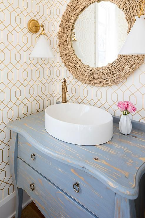 Gorgeous powder room with a distressed gray Bombay chest and round vessel sink are surrounded by gold trellis wallpaper and a round rope mirror.