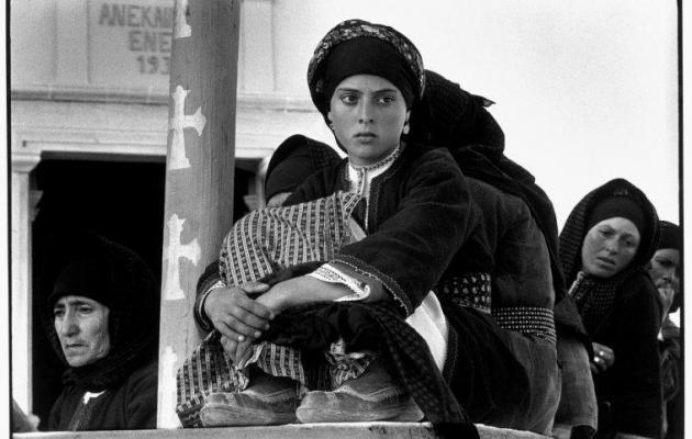 En 1964, cette jeune femme grecque observent un spectacle de danse. Elle est vêtue d'habits et d'une coiffe traditionnelle.  [CONSTANTINE MANOS / MAGNUM PHOTOS ]