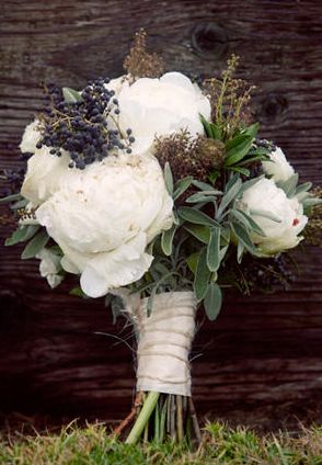The bridal bouquet will be a loose clutch of ivory peonies, blue privet berries, green sage, white gardenias, rosemary, seeded eucalyptus and dusty miller wrapped in ivory linen.