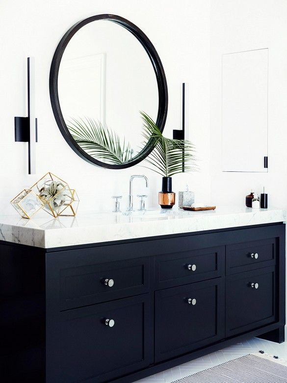 This bathroom featuring black cabinets, a round mirror, and marble countertop by Consort Design was surprisingly done on a budget