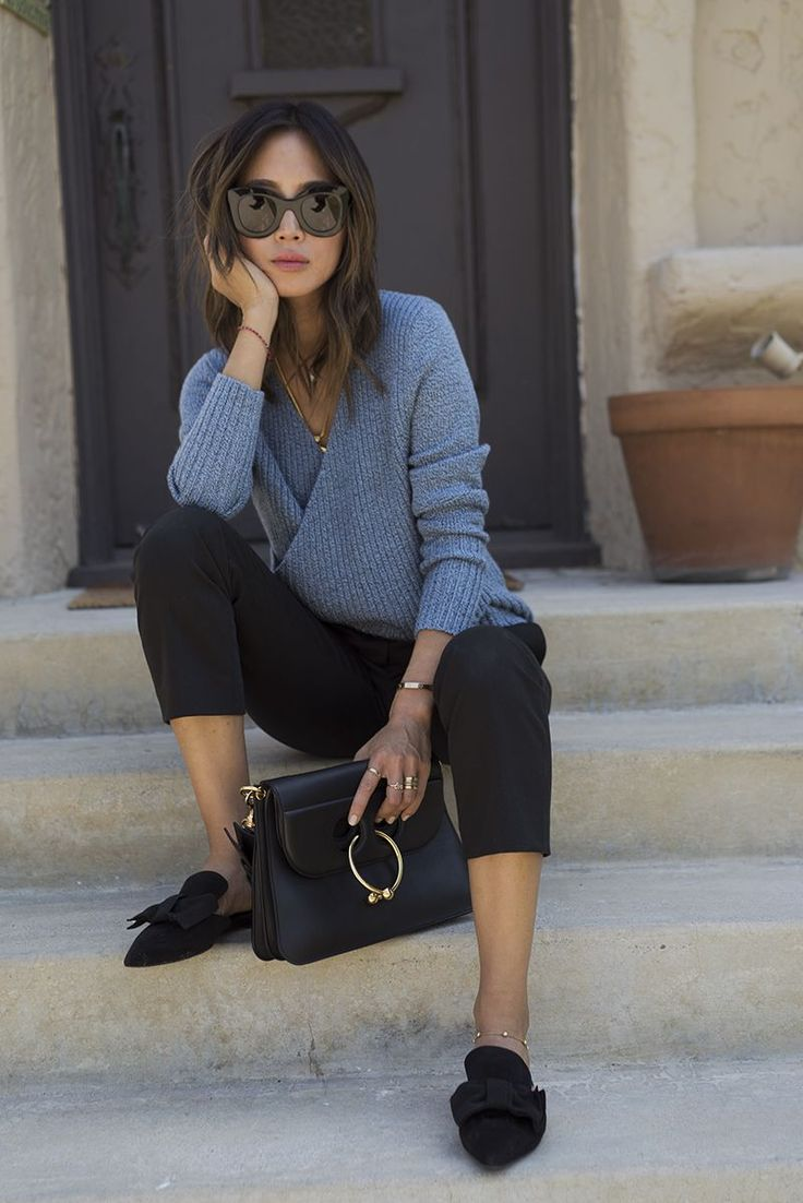 Relaxed minimal outfit with gray sweater, tapered pants, and slides.