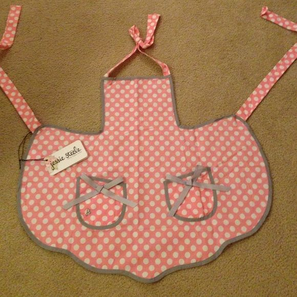 NEW Jessie Steele Apron Brand New With Tag Jessie Steele Apron. Darling pink and white polka dot pattern with gray trim! Adorable bow details! Approx. 25 inches long and 29 inches wide. Jessie Steele Accessories