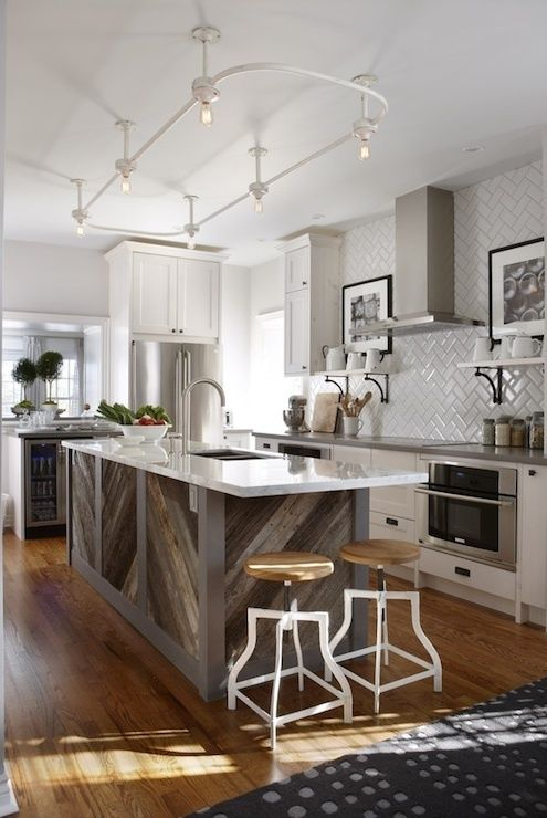 Ramsj  source: Sarah Richardson Design Stunning kitchen with gray walls paint color, Ikea kitchen cabinets with Silestone Grey Expo countertops, barnboard kitchen island with calcutta marble countertop, barnboard backsplash, subway tiles in herringbone pattern backsplash, swivel stools from Morba, wine cooler and vintage shower enclosure lighting.   Para Paints Mennonite Grey     view 5 more ...