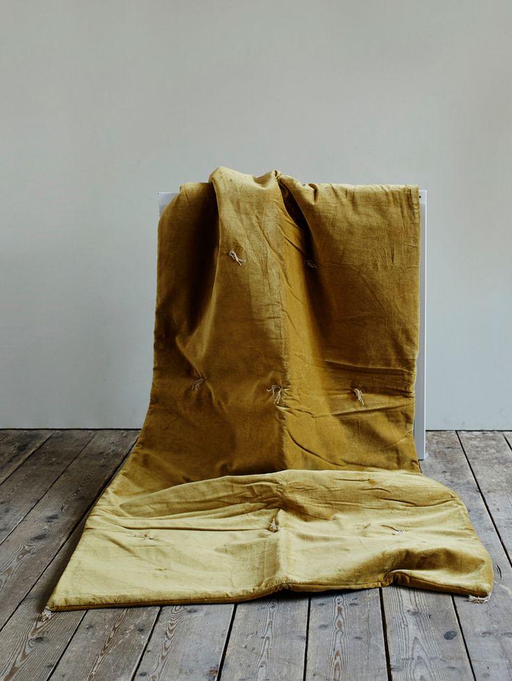 En accessoar som skyddar armstöd, rygg eller sittdynan på din soffa. Gjord i sammet med broderade tofsar av garn.