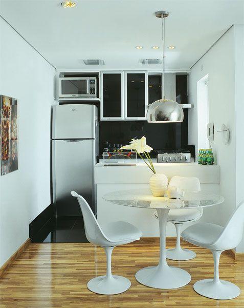 Com 46 m², este duplex foi personalizado. Materiais diferentes na cozinha e no living caracterizam os diferentes espaços. O piso de porcelanato preto contrasta com a bancada de laminado branco, destacando esta área da cozinha. Eletrodomésticos embutidos auxiliam na otimização do espaço.  modo slideshow
