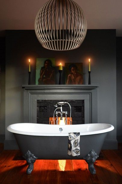 The Salcombe Cast Iron Bath in front of fireplace the warmth of the fire and Farrow & Ball's 'downpipe' make the bathroom cosy and dramatic