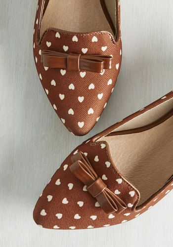 Hurry your feet into these fabric flats so you, too, can experience the pure adoration they incite! Boasting a white heart print, glossy piping, and double bows topping their pointed toes, these brown shoes by Restricted are your latest fashion flame.