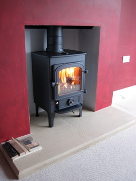 Clearview Pioneer 400 in Charcoal metallic with brass handles on 6 inch legs - installed with a Bathstone hearth hand-made by Nicholas Curtis; fire chamber lined with Calcium Silicate board - to a detached 1930's house in a quiet leafy road in Farnham, Surrey.