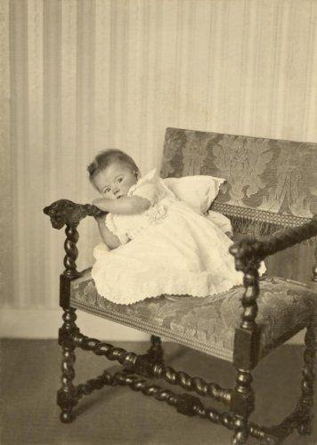 Een peuter -met rode koontjes-, gekleed in een witte jurk houdt zich vast aan de armleuning van een stoel met gedraaide poten en armleuningen. De stoel staat voor subtiel gestreept behang, de stoel zelf is bekleed in velours. Vermoedelijk in of nabij Bloemendaal, tussen 1912-1922.