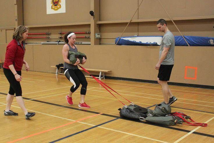 Joanne Courtney, deuxième joueuse de l'équipe féminine de curling  d'Équipe Canada, démontre sa force en tirant des sacs contenant 130 kilogramme de sable sur le plancher du gymnase de la 15e Escadre Moose Jaw (Saskatchewan). Deux membres de l'équipe se sont entraînées avec le personnel du 15e Escadron de contrôle de la circulation aérienne lors d'une visite à l'escadre. PHOTO : Captain Susan Magill