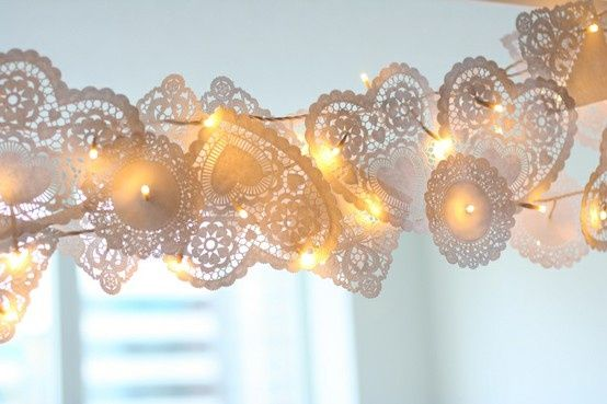 Doily Garland. This gorgeous garland would be very simple to make using inexpensive paper doilies and strings of Christmas lights.  This would be beautiful over a dessert or candy buffet table or to decorate the ceiling for a tent wedding.