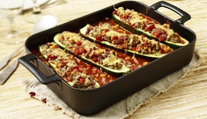 Zucchini in Hälften schneiden und mit knackigem Mais, bunten Paprikastückchen, deftigem Hackfleisch und cremigem Frischkäse füllen und ab in den Ofen!