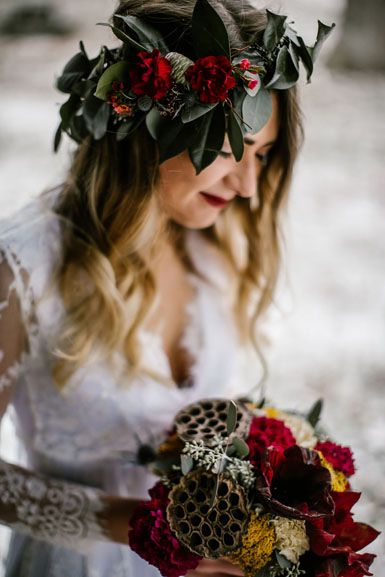 Outdoor winter wedding bride's bouquet flowers featuring red amaryllis brown lotus pods gold yarrow and hair flower crown of camelia by www.redpoppyfloral.com