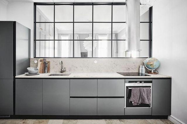 Jag föll pladask för materialkombinationen i det här köket. Sandfärgat mot mörkt grått, där svarta detaljer och fönstret som delar av med ett ljusgenomsläpp mot sovrummet utgör en distinkt grafisk kon