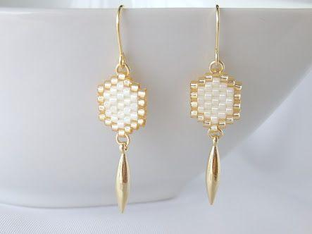 Boucle d'oreille octogonale blanche et dorée avec breloque