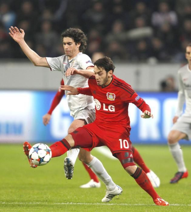 Bayer Leverkusen's Hakan Calhanoglu challenges Atletico Madrid's Tiago Mendes (L) during their Champions League round of 16, first leg soccer match in Leverkusen February 25, 2015.