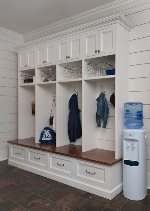 Fantastic mudroom boasts tongue and groove paneled walls used as a backdrop to open and closed mudroom lockers, one for each family member, atop a built-in mudroom bench with drawers for extra storage.