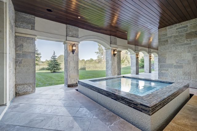 Tucked beneath a covered porch sits a private spa that is perfect for relaxing or entertaining. For more information, visit us at VintageLuxuryHomes.com  #design #house #dreamhome #backyard #luxury #luxurydesign