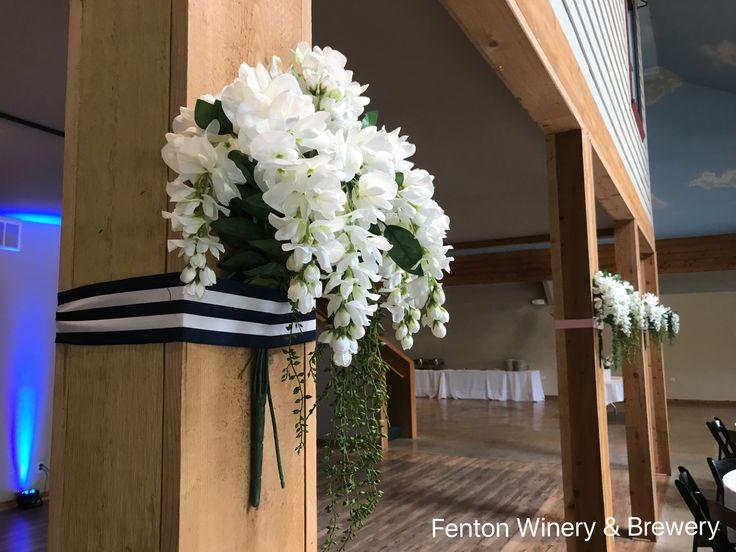 Simple silk flower display ribbon tied to the pillars makes for an easy DIY wedding decor idea. #michiganweddings #weddingvenue #fentonwineryandbrewery