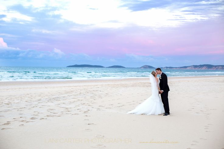 Bride and groom kissing on the beach at sunset. Rainbow beach wedding. www.lanicarter.com