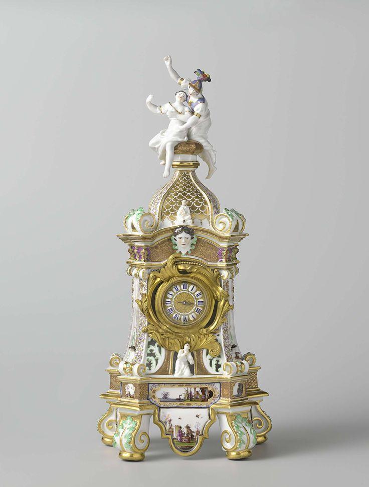 Meissener Porzellan Manufaktur   Mantel clock (pendule) with Arachne and Athena, Meissener Porzellan Manufaktur, George Fritzsche, Barrey, 1727   Schoorsteenklok met beschilderd porselein. De klok heeft een trapeziumvormige basis. De vier overhoeks geplaatste poten staan op vergulde ringen en zijn in reliëf versierd met een acanthusblad. Het lichaam wordt bekroond door een gewelfde koepel waarop twee vrouwenfiguren. Het onderste deel van drie wanden van het lichaam is aan weerszijden van een…