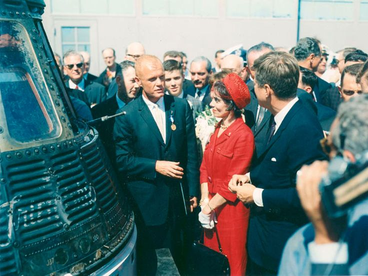 John Glenn, standing next to his Friendship 7 capsule in which he made his historic orbital flight, meets with President John F. Kennedy. Mrs. Glenn stands next to her husband. Earlier that day, President Kennedy presented the NASA Distinguished Service Award to Glenn.