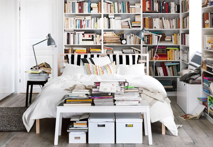 A modern bedroom with a large white bed in the middle of a white room surrounding the bed is a lots of bookshelves loaded with books in different colours.
