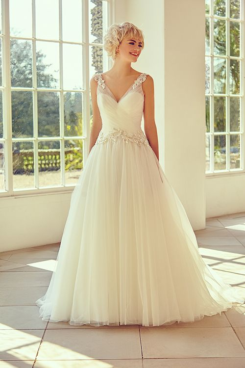 A ball-gown style dress with embellished applique and tulle. <strong>Size: </strong>8 – 30 <strong>Colour: </strong>Ivory <strong>Fabric:</strong> Embellished applique, tulle <strong>Style:</strong> Ball gown <strong>Neckline:</strong> V-Neck <strong>Laced or Zipped: </strong>Zipped