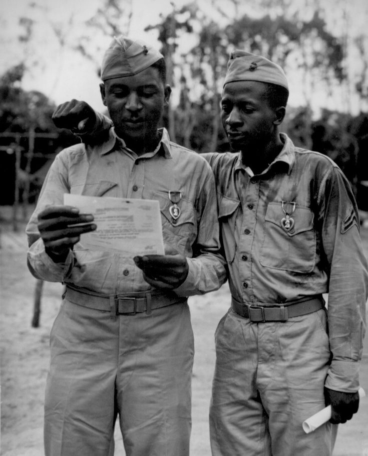 """""""First Negro Marines decorated by the famed Second Marine Division somewhere in the Pacific (left to right) Staff Sgt Timerlate Kirven...and Cpl. Samuel J. Love, Sr... They received Purple Hearts for wounds received in the Battle of Saipan..."""""""