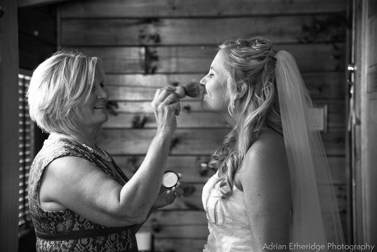 Mother of the bride putting the finishing touches on her daughter's makeup.
