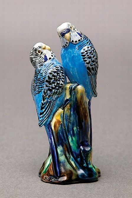 Pottery figural group of two budgerigars perched on a stump, modelled with blue markings, the base incised 'Grace Seccombe NSW'.
