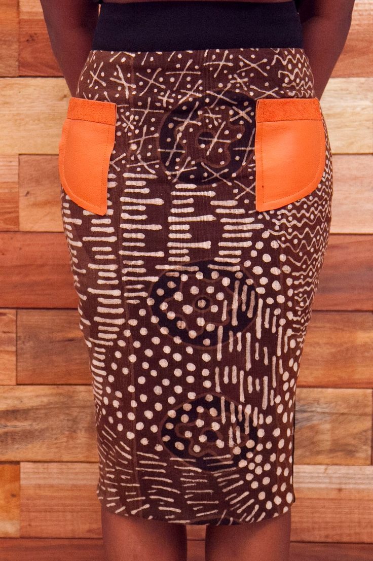 Totally Ethnik Basics Collection, Ready-to-wear Modern African Pencil Skirt, Bogolan (mud cloth) and orange Leather Pocket. Back of the skirt is plain Black, stretch fabric