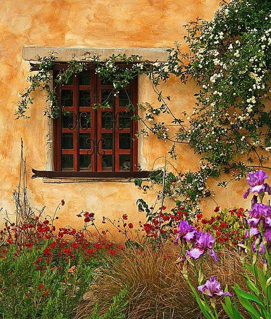 The Fairytale Cottages of Carmel By-the-sea! Love the red panes, the flowers climbing the walls, the beam over the window.