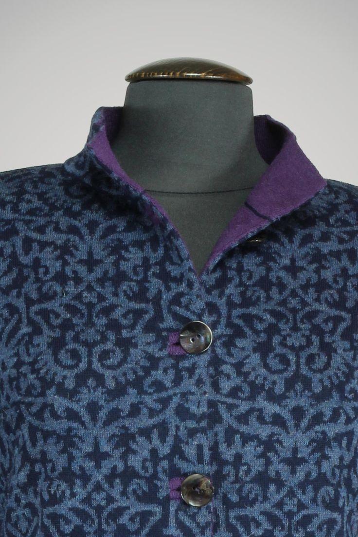 Het vest is gebreid in een twee kleurig jacquard motief. De contrasterende paarse kleur van de knoopsgaten en binnenkant van de kraag geven deze klassieke jas een geraffineerd accent.  Kleuren: donkerblauw,denim blauw, paars.