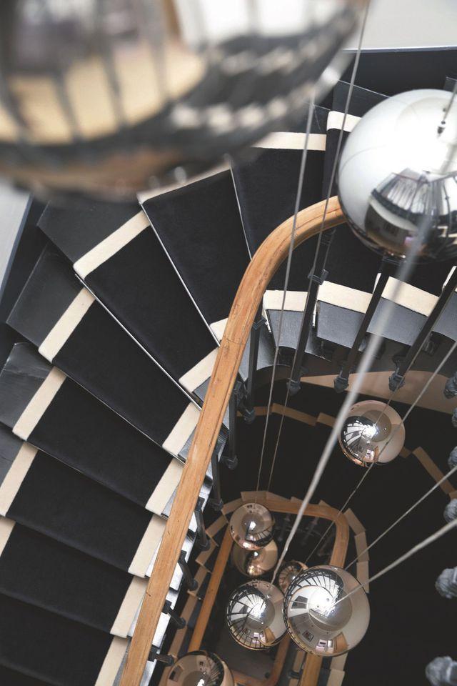 """Dans l'escalier, une sculpture géante de suspensions """"Mirror Ball"""" de Tom Dixon et un tapis de sol, Garotex."""