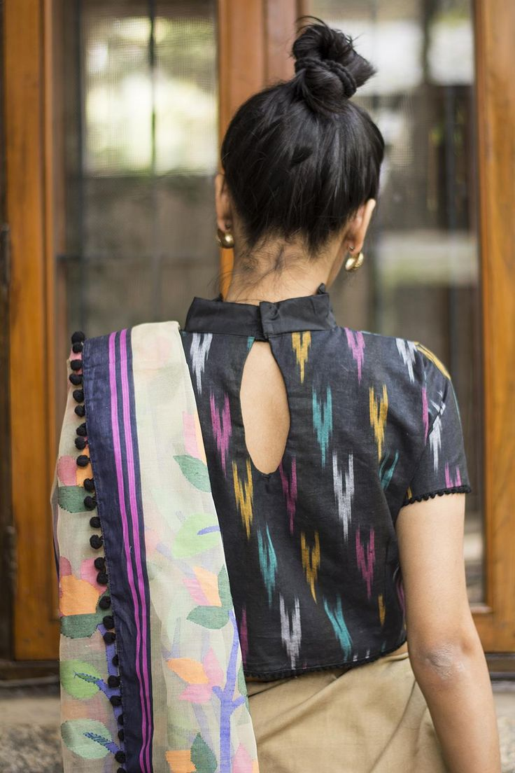 A stylish black criss cross front high back style in Ikat. A black collar and faux placket, with black pom pom edged sleeves and body. Ikat is today's earthy trend!Pair with any of the colours in the Ikat print and never go wrong. Or do a black handloom and be the mysterious sophisticate. Whatsapp +91 81050 68601. *Shipping worldwide* #saree #blouse #sareeblouse #blousedesigns #desi #indianfashion #india #bollywood #black #ikat #cotton